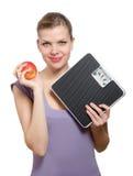 Femme retenant une échelle de poids et une pomme rouge Photographie stock