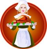 Femme retenant une dinde rôtie d'une plaque Image stock