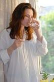 Femme retenant une pillule et une glace de l'eau Images stock