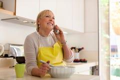 Femme retiré préparant la nourriture à la maison Photos libres de droits