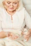 Femme retirée âgée prenant des pilules à la maison Photographie stock libre de droits