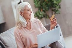 Femme retirée agréable employant des opérations bancaires en ligne à la maison Photos libres de droits