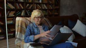 Femme retirée agréable faisant sa planification fiinancial à la maison banque de vidéos
