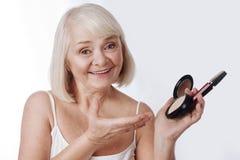 Femme retirée agréable tenant la poudre de visage et le mascara Photographie stock libre de droits