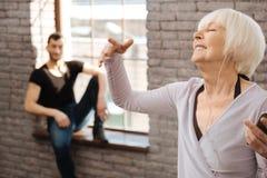 Femme retirée avec plaisir appréciant la musique pendant la classe de danse Photos stock