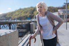 Femme retirée ayant une douleur plus lombo-sacrée pendant la promenade Image libre de droits