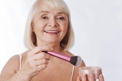 Femme retirée belle tenant une brosse de maquillage Image stock