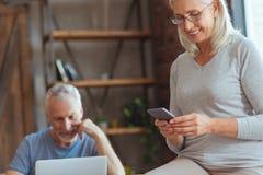 Femme retirée joyeuse à l'aide de son téléphone intelligent Photographie stock libre de droits