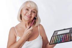 Femme retirée joyeuse tenant une palette de fard à paupières Image libre de droits