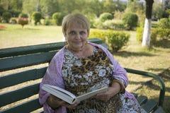 Femme retirée lisant un livre sur le banc Photo stock