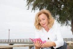 Femme retirée par aîné avec le smartphone extérieur Image stock