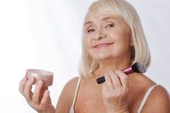 Femme retirée par positif employant une brosse de maquillage Image stock
