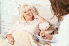 Femme retirée parlant au docteur dans l'hôpital images stock