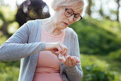 Femme retirée prenant des pilules en parc Photographie stock libre de droits