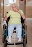 Femme retirée sur le fauteuil roulant Photo stock