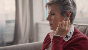 Femme retirée utilisant les écouteurs modernes et blancs banque de vidéos