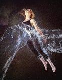 Femme réfléchie dans l'éclaboussure de l'eau flottant en air Photos stock