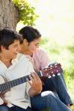Femme riant avec son ami qui joue la guitare Photographie stock