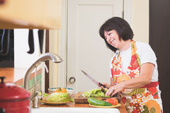 Femme riant tout en coupant la laitue dans la cuisine Image libre de droits