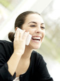 Femme riant tout en parlant au téléphone portable Photos stock