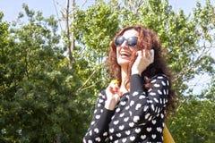 Femme riant tout en parlant la baie le téléphone Photographie stock