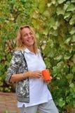 Femme riante avec une tasse orange dans la cour du sud Images libres de droits