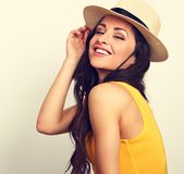 Femme riante de beaux longs cheveux dans le dessus et le chapeau de paille jaunes l Photos stock