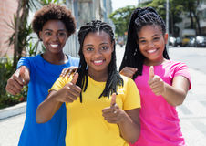 Femme riante de l'afro-américain trois montrant le pouce  Image stock