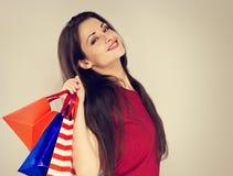 Femme riante enthousiaste de jeunes avec des sacs à provisions recherchant et pensant sur l'espace bleu de copie photo stock