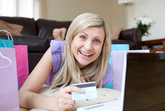 Femme riante faisant des emplettes en ligne se trouvant sur l'étage Images libres de droits