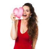 Femme riante retenant un coeur d'amour au-dessus de son oeil. Photos libres de droits