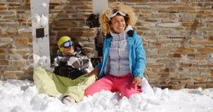 Femme riante s'asseyant à côté de l'ami dans la neige Photos stock