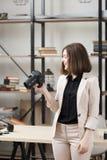 Femme riante se tenant avec l'appareil-photo au bureau Image stock