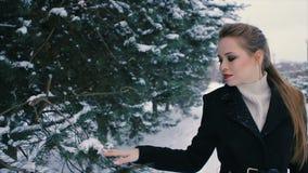 Femme riche de brune dans le manteau noir sur le fond du mouvement lent d'arbre de Noël banque de vidéos