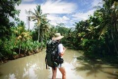 Femme risquée avec le sac à dos se tenant près de la grande rivière tropicale et regardant loin Photographie stock