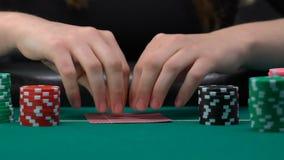 Femme risquée sûre vérifiant ses cartes et paris en hausse, bluff pour la grande victoire banque de vidéos