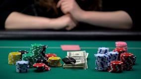 Femme risquée soulevant des enjeux au jeu de poker, mettant la clé d'argent et de voiture sur la table images stock