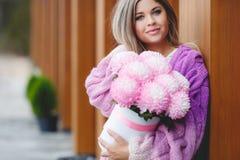 Femme romantique avec des fleurs dans leurs mains Images stock