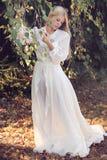 Femme romantique parmi des feuilles d'automne Photos stock
