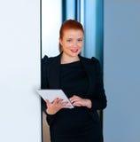 Femme rouge d'affaires de cheveux avec le comprimé dans le bureau Image libre de droits