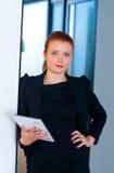 Femme rouge d'affaires de cheveux avec le comprimé dans le bureau images libres de droits