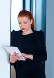 Femme rouge d'affaires de cheveux avec le comprimé dans le bureau Photo stock