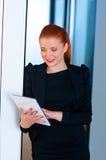 Femme rouge d'affaires de cheveux avec le comprimé dans le bureau Image stock