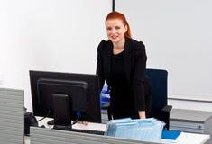 Femme rouge d'affaires de cheveux dans le bureau photo stock