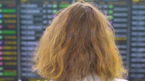 Femme rouge de fille de gingembre de cheveux vérifiant le conseil de départ à l'aéroport, du dos banque de vidéos
