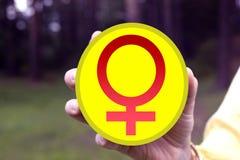 Femme rouge de symbole dans sa main photo stock