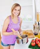 Femme rougeoyant faisant cuire des spaghetti à la maison Image stock