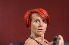 Femme rousse adulte choquée regardant l'appareil-photo Image libre de droits