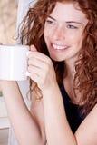 Femme rousse assez jeune avec les taches de rousseur et le coffe images stock
