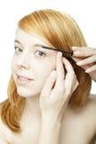 Femme rousse attirante appliquant le mascara photographie stock libre de droits